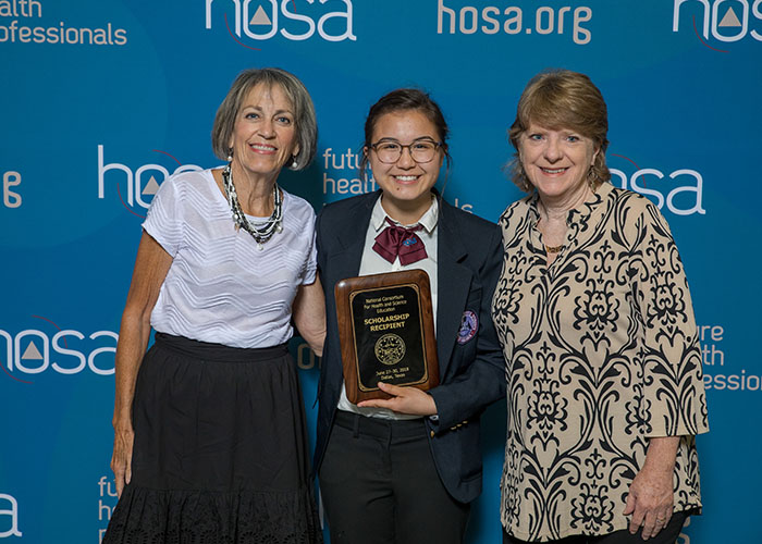 Adults posing with student who won an award